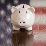 Piggy Bank with an American Flag Reflection on Wooden Table.